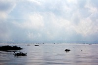 A dramatic cloudscape on Inle Lake, Burma, with a lone person on a boat in distance