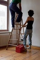 A woman holding a ladder while a man steps up