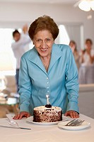 A senior woman with a cake