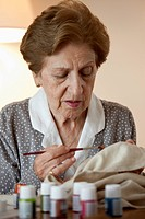 A senior woman painting on fabric
