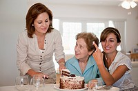 A woman serving cake for her mother and daughter (thumbnail)