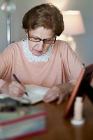 A senior woman writing in a note book