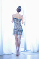 Rear view of a woman in see through nightgown looking out a window