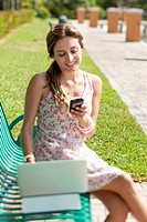 A woman sitting on a park bench using a laptop and a mobile phone