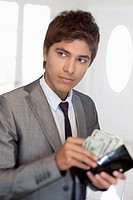A businessman taking money out of his wallet