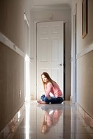 Girl sitting cross-legged in hallway (thumbnail)