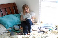 Busy girl with study books on bed (thumbnail)