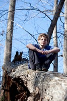 Boy sitting on broken tree trunk