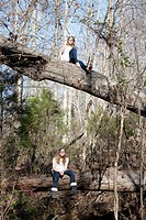 Two similar girls sitting on tree trunks in forest in Mooresville, North Carolina, USA