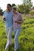A couple walking outdoors arm in arm with red wine