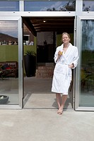 A woman standing in the doorway of her house in a bathrobe enjoying the morning