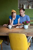 A man talking about his journal to his girlfriend at the dining table