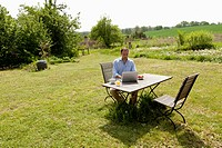A man sitting at a table in his backyard having breakfast and using a laptop