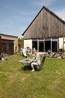 A woman using a laptop and having breakfast in her backyard (thumbnail)