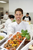 Portrait of male chef holding salad with coworkers in background
