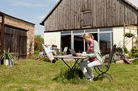 A woman using a laptop and having breakfast in her backyard