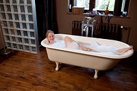 A woman taking a bubble bath and winking playfully