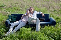 A couple sitting on a sofa in a field of grass