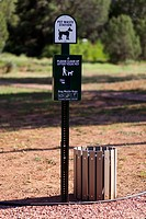 A sign and bin for pet waste in a park