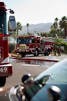 A fire truck and firefighters on a suburban street next to a burning house (thumbnail)
