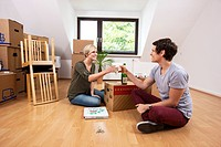 Young couple sitting in an empty room in a new apartment and raising their glasses of champagne to celebrate moving in together