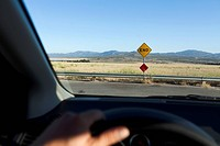 View through a car windshield of an END road sign and mountain ranges behind