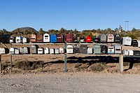 Rows of mailboxes next to a dirt road in a desert