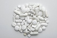 A heap of various white pills and capsules