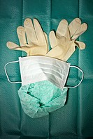Surgical mask, cap and gloves arranged on a surgical drape