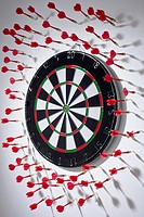 Multiple darts stuck in a wall all around a dartboard