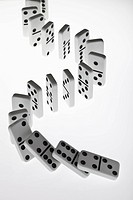 Dominoes in a row, beginning to fall over in a chain reaction