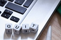 Lettered cubes on a laptop spelling QUIT