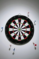 Darts stuck in a wall all around a dartboard