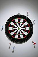 Darts stuck in a wall all around a dartboard