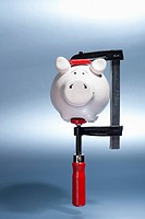 A piggy bank being held in a vise grip suspended in mid-air (thumbnail)