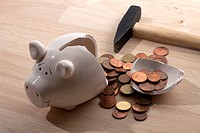 A hammer lying next to a broken piggy bank with Euro coins spilling out