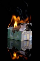 European Union currency folded into a house and on fire