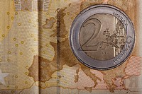 Detail of a fifty Euro banknote with a two Euro coin on top of it (thumbnail)