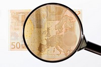 A magnifying glass magnifying a fifty Euro banknote