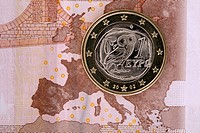 Detail of a ten Euro banknote with a one Euro coin on top of it