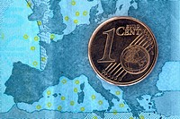 Detail of a five Euro banknote with a one cent Euro coin on top of it