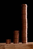 Three rows of stacks of copper coins increasing in size