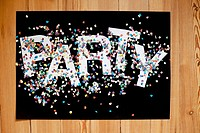 Confetti and letters spelling PARTY on a black poster board (thumbnail)