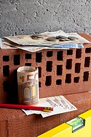A pile of money on stacked bricks with a pencil and level