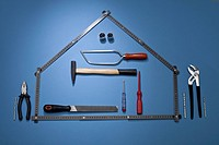 A folding ruler arranged to look like a house with various work tools