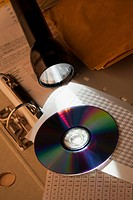 A flashlight illuminating a compact disc on top of a spreadsheet and binder
