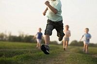 Low view of a boy running in a field with other children behind (thumbnail)