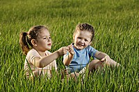 Two young girls sitting in a field (thumbnail)