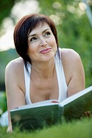 A mature woman lying down on grass with a book