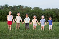Portrait of children holding hands in a field